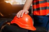 Hand of worker man in safety orange helmet near steel pipes. - 143909968