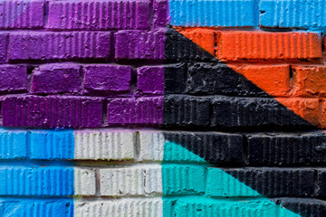 Brick wall with fragment of graffiti, abstract drawings art close-up. For background. Concept of Modern iconic urban culture, Bright shades of different colors