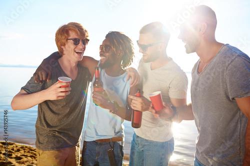 Billede Cheerful buddies enjoying beach party on hot day