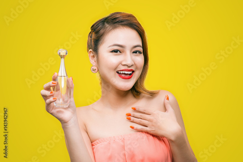 Cheerful beautiful asian young woman with charming smile holding perfume over yellow background