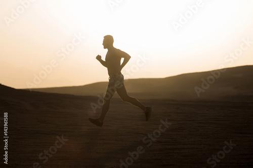 Man runner running in dune at sunset