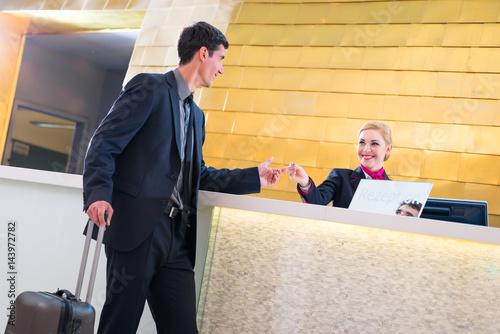 Mann beim Check-In an Rezeption oder Front Office eines Designhotels