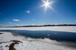 The river is covered with melting ice on a sunny spring day