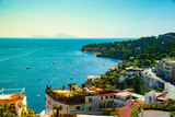 Naples bay scenic view, Italy. Travel background picture with blue sea and cityscape in golden light of evening.