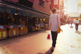Young woman walking on the street in Asakusa Tokyo at sunset looking ahead