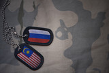 army blank, dog tag with flag of russia and malaysia on the khaki texture background. military concept