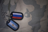 army blank, dog tag with flag of russia and argentina on the khaki texture background. military concept