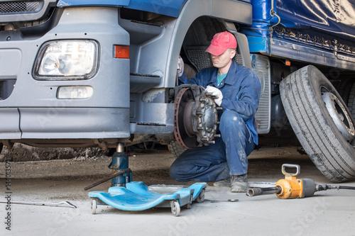 Fototapeta Mechanic repair truck is on the Jack