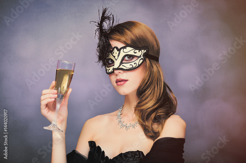 Poster photo of beautiful young woman in mask with wineglass of champagne on the wonder
