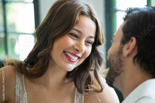 Smiling woman looking at man in restaurant