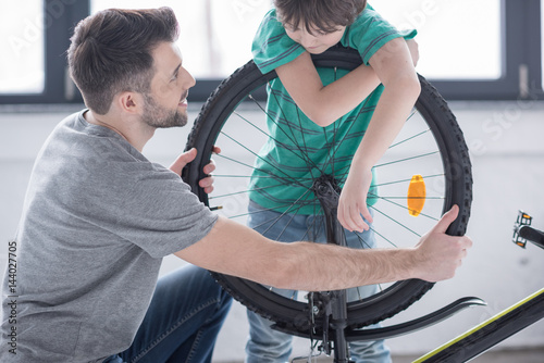 side view of father and son repairing bicycle together on white