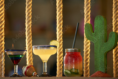 Burning cocktail in shot glasses on colorful background