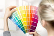 Quadro woman selecting home interior paint color from swatch catalog