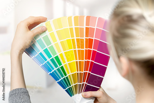 woman selecting home interior paint color from swatch catalog Poster