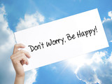 Don't Worry, Be Happy! Sign on white paper. Man Hand Holding Paper with text. Isolated on sky background