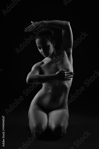 Art nude, perfect naked body, sexy young woman on dark background, black and white studio shot