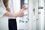 Locking or unlocking door with key in hand - 144059521