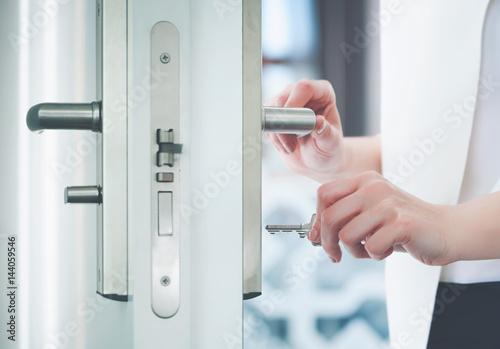 Locking or unlocking door with key in hand Poster