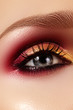 Closeup female eye with fashion bright make-up. Beautiful gold, red eyeshadow, glitter, black eyeliner. Shape Eyebrows