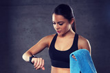 young woman with heart-rate watch and towel in gym