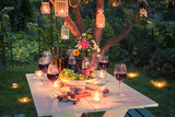 Beautiful table full of wine, cheese and snacks at dusk - 144076197