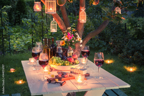 Foto Murales Beautiful table full of wine, cheese and snacks at dusk