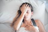 Donna con mal di testa a letto, emicrania e sinusite  - 144083729