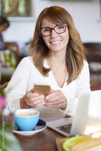 Shot of a middle aged woman making call and working on laptop while sitting at cafe.