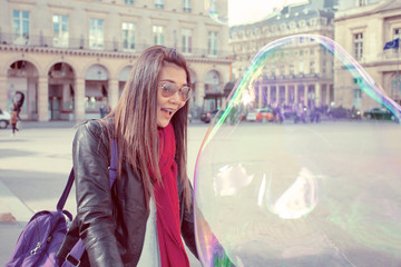 Asian woman blowing a big colorful soap bubble.