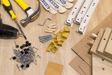 Furniture assembly components and tools arranged in a still life on a table. - 144093773
