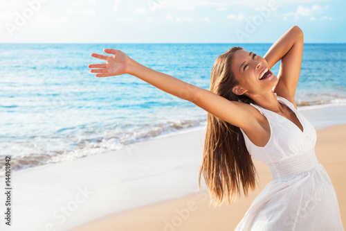 Leinwanddruck Bild Freedom woman on beach enjoying life with open arms feeling free bliss and success on beach. Happiness Asian girl in white summer dress enjoying ocean nature sunset during travel holidays vacation.