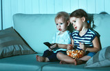 Fototapety Children brother and sister watching TV in evening