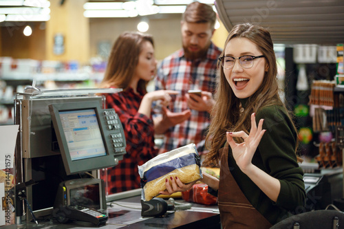 Cashier woman on workspace make okay gesture.