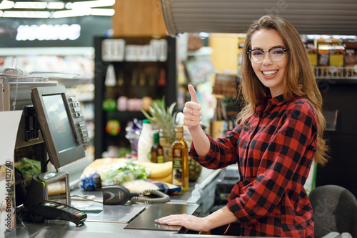 Cheerful cashier woman on workspace showing thumbs up.