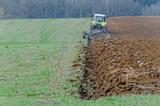 Traktor uprawiający ziemię na polu.