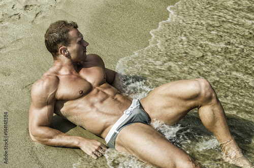 Handsome young bodybuilder smiling, laying down on the beach sand