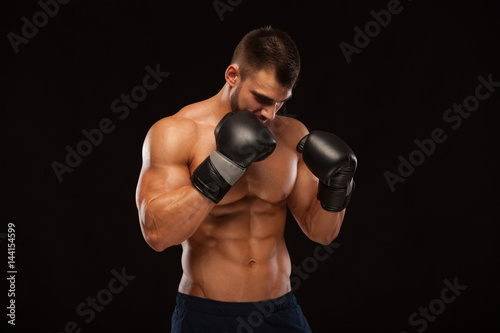 Muscular young man with perfect Torso with six pack abs, in boxing gloves is sho