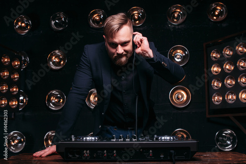 Poster Young disk jockey with headphones and mixer checking equipment
