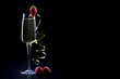 champagne sparkling white wine glass and bottle on black background with strawberry garnish gold ribbon