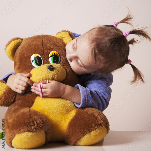 Beautiful baby girl playing and  kissing teddy bear (Childhood, joy, serenity) Poster