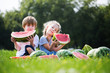 Funny kids eating watermelon outdoor.