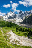 Beautiful green Adyl-Su gorge with a rough river in sunny summer day. Greater Caucasus mountains, Kabardino-Balkaria, Elbrus region.