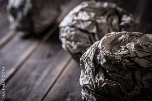 crumpled paper balls on wooden table Poster