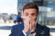 Young man in suit manager sneezes on the street covering his face with his hands. Allergic reaction in the spring on the street.
