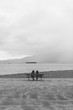 Two people sit on a bench looking out towards English Bay, Vancouver BC.