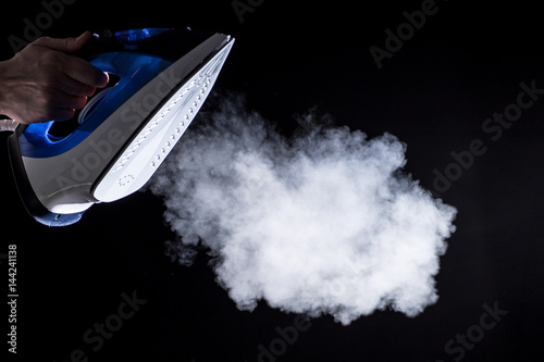 Modern iron blowing off steam on background Poster