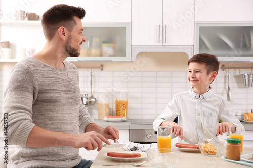 Dad and son having lunch at home © Africa Studio