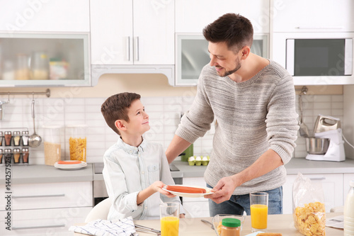 Dad and son preparing to have lunch at home © Africa Studio
