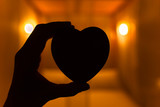Romance in the bedroom concept. Hand holding heart in a softly lit bedroom.  - 144258588