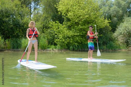 Juliste Couple paddling on boards